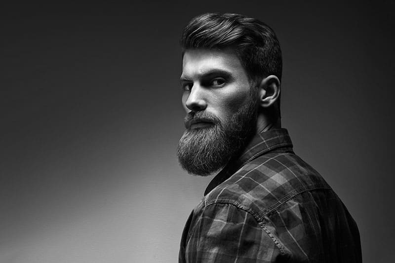 Black and white photo of bearded stylish businessman Handsome confident perfect hairstyle man indoor .