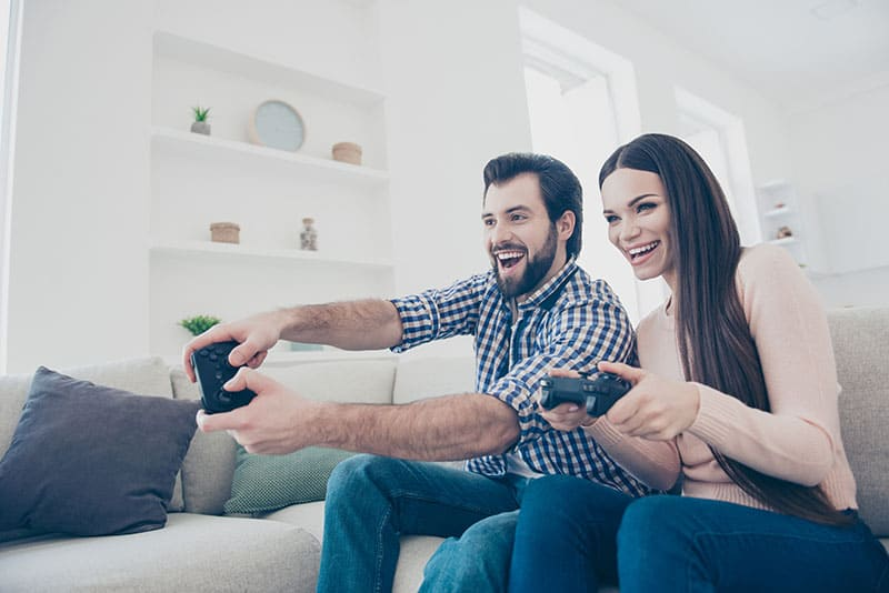 Portrait of cheerful active couple enjoying playing videogame