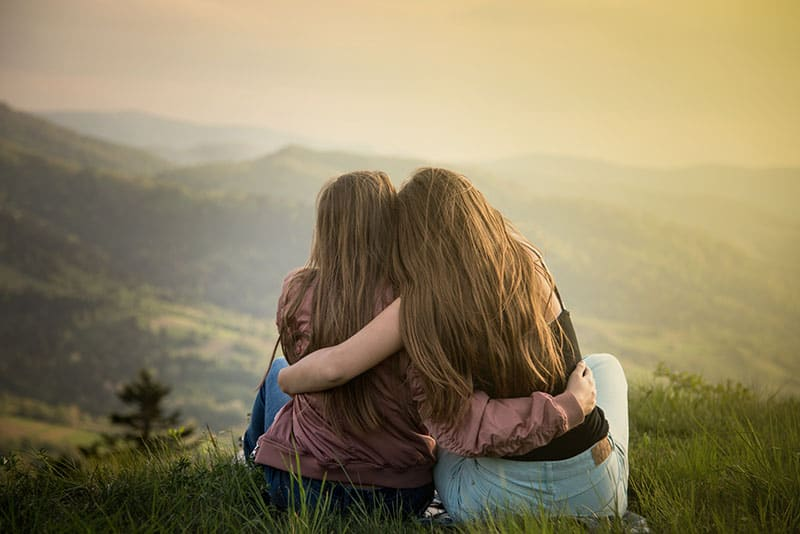 Two friends hugging looking at the Carpathians mountains. Two girls on top of the mountain watching at sunset.