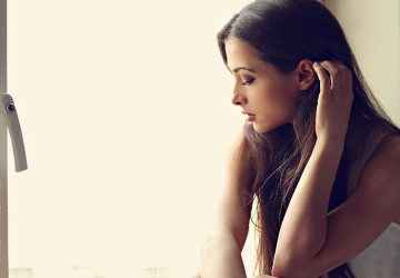 Beautiful sad lonely woman in profile view thinking about and looking though the window. Closeup