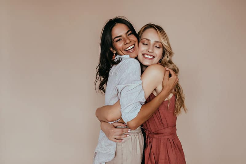 Pretty girls with trendy makeup embracing on light background. Excited caucasian sisters expressing love