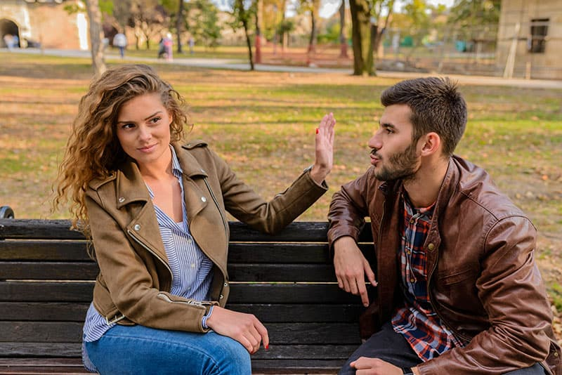 Young man and woman angry and conflicting on a park bench