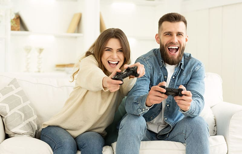 Fans Of Xbox. Crazy Couple Enjoying Playing Videogame On Playstation, Resting At Home