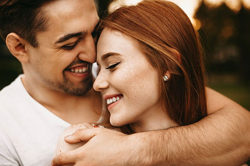 Close up portrait of a amazing young female with red hair and freckles smiling with closed eyes while being embraced from back