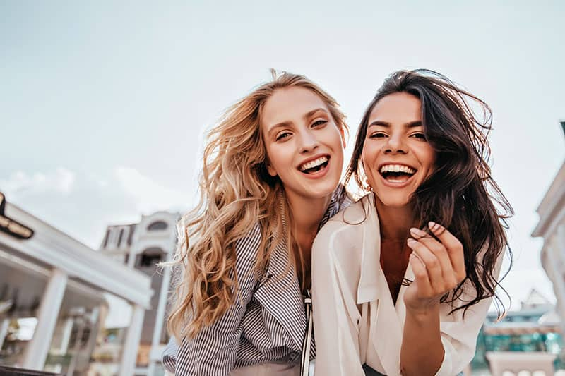 Appealing long-haired girls posing on sky background. Laughing ladies enjoying weekend together