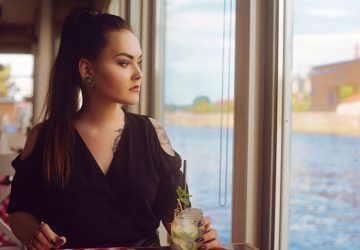 The girl in a restaurant on the ship near the river drinks mojito. Brunette with tattoo looks out the window and drinks mojito in a glass jar. The girl with the tunnels in the ears.