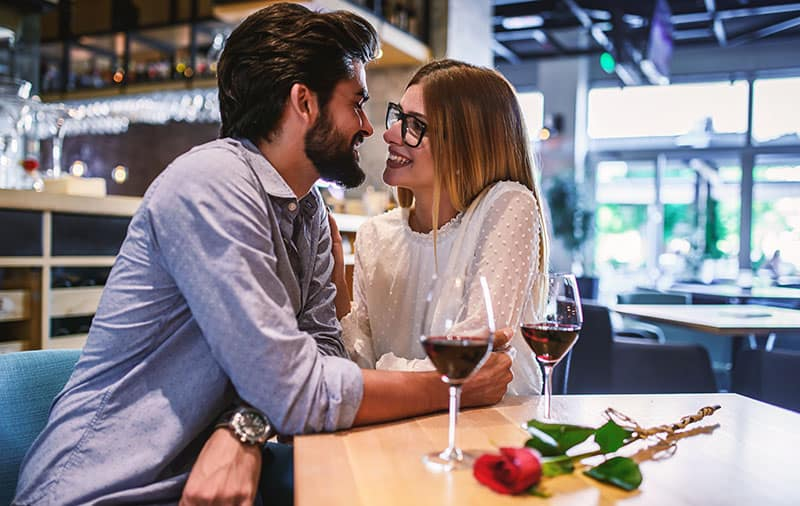 Dating in the cafe. Romantic couple drinking wine and enjoying in conversation. Dating, love, relationships