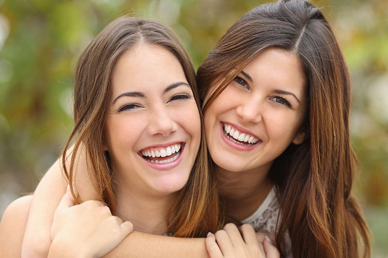 Two women friends laughing with a perfect white teeth with a green background