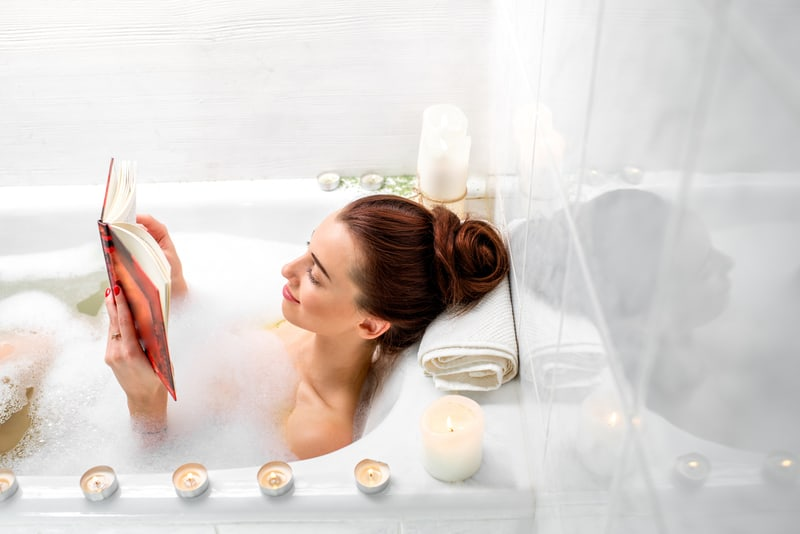 woman reading book while lying in the bath