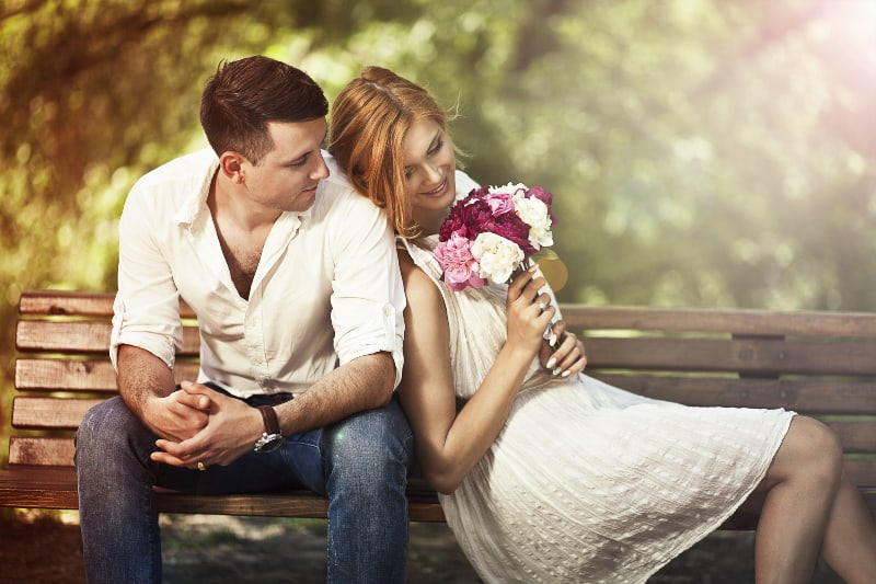 woman with flowers sitting with boyfriend