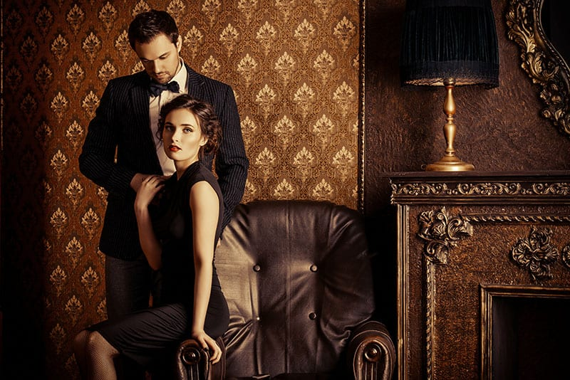 Beautiful man and woman in elegant evening clothes in classic vintage apartments. Glamour, fashion. Love concept