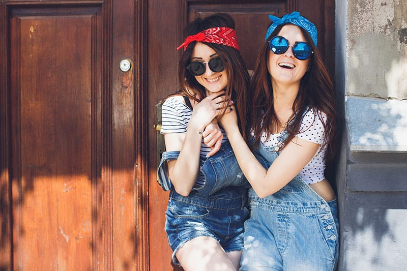 eautiful young brunette twins sisters, in stylish sunglasses, hugging and laughing. Having fun time together