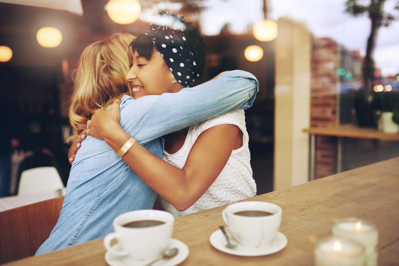 Two multi ethnic affectionate girl friends embracing as they sit in a coffee