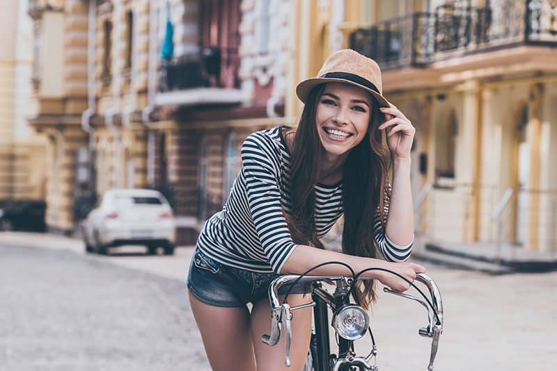 Funky beauty. Beautiful young woman leaning at her bicycle and smiling while standing outdoors