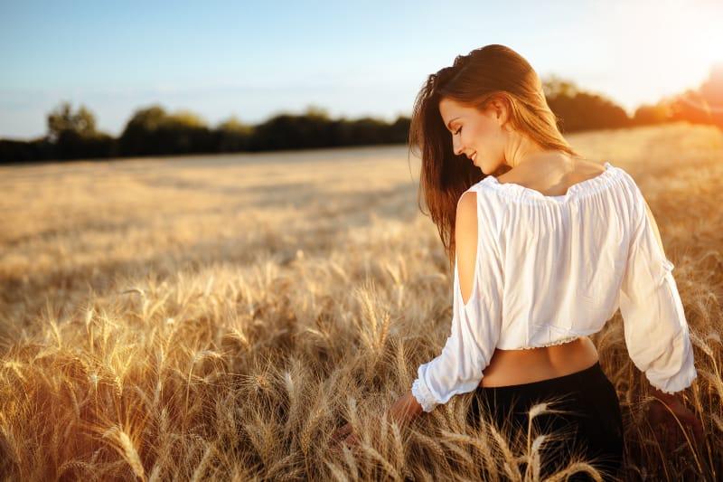 Romantic woman walking in golden fields