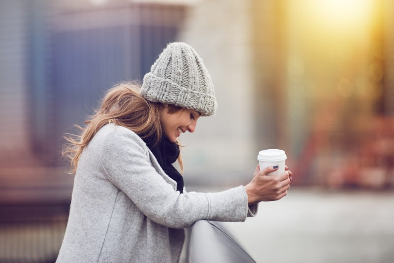 Beautiful happy young adult woman drinking coffee