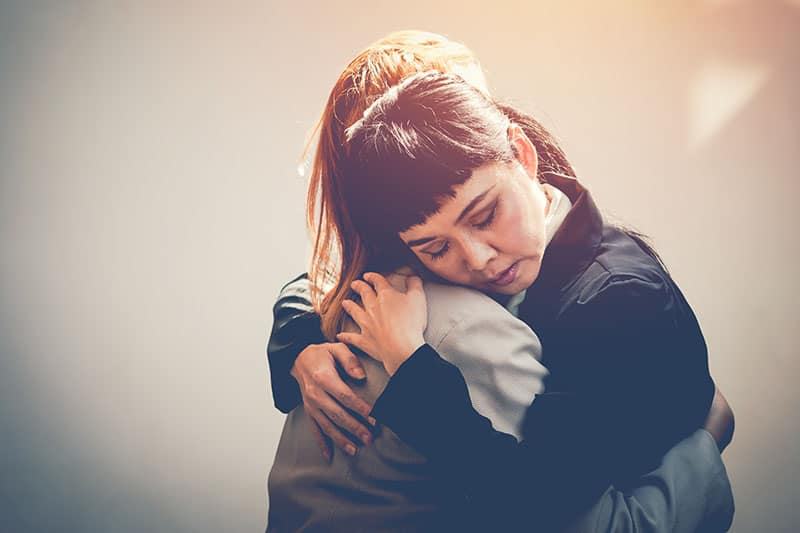 Two women hug to console