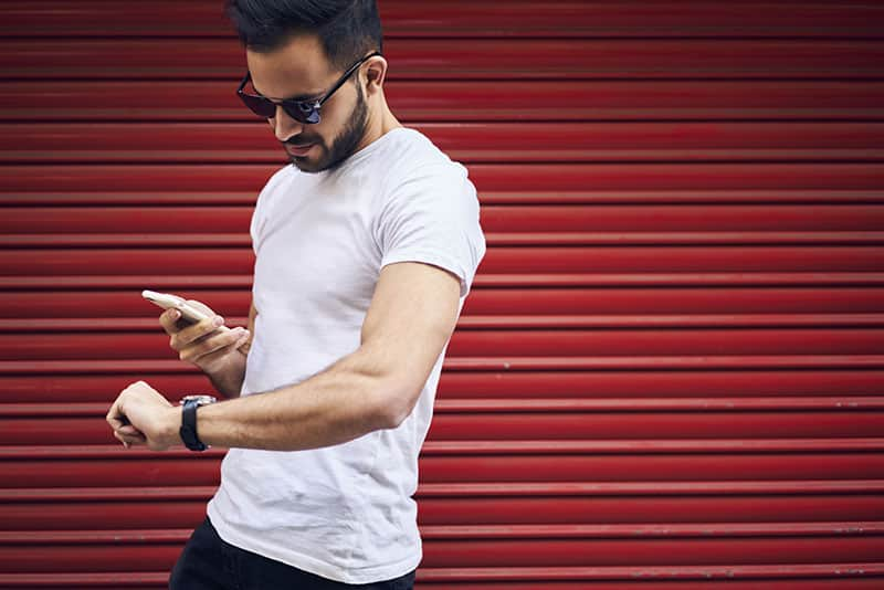 Handsome young bearded man in eyewear and casual outfit receiving text mail with invitation for meeting in cafe strolling outdoors hurrying to get there in time passing copy space for advertising