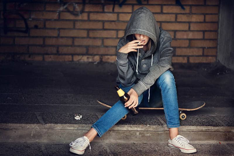 Teen girl in hood holding a beer bottle and smoking the cigarette