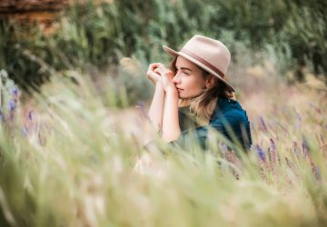 Summer portrait of young hipster woman sitting in a grass