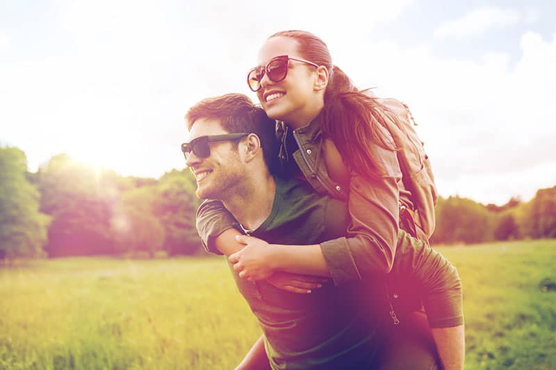 travel, hiking, backpacking, tourism and people concept - happy couple in sunglasses with backpacks having fun