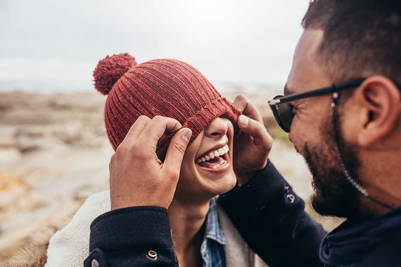 Loving couple having fun outdoors. Man covering eyes of woman with cap