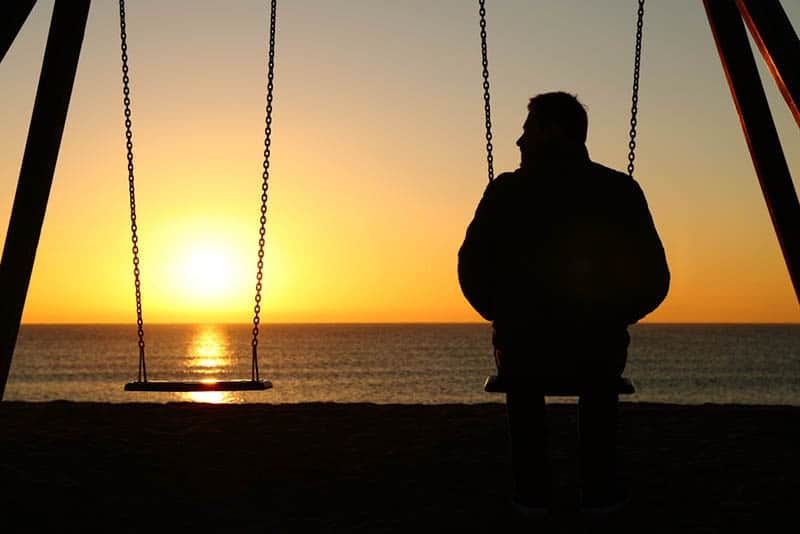 silhouette of man sitting on swing in front of sea