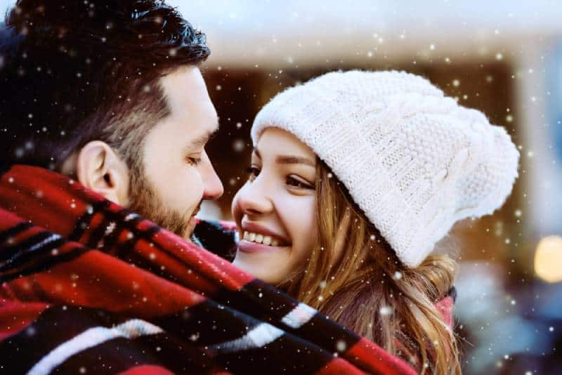 smiling couple looking at each other on winter
