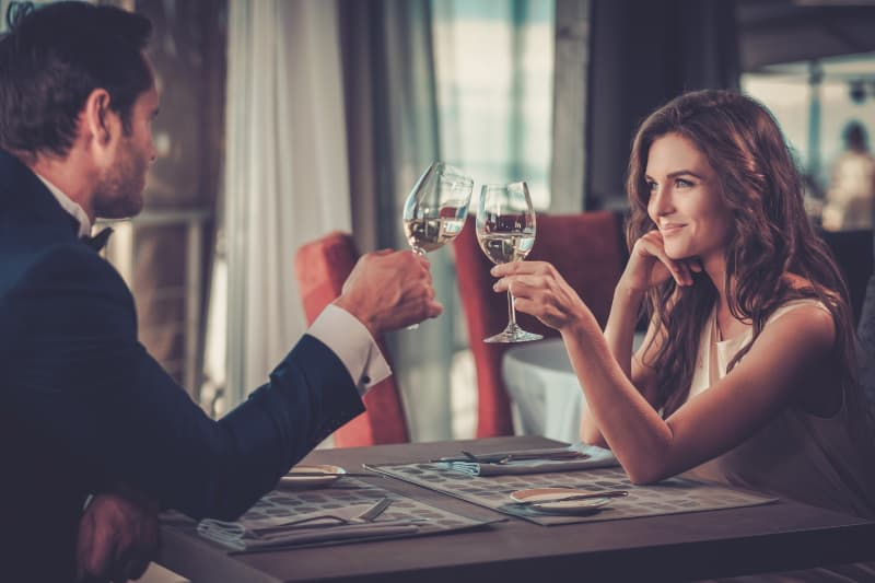smiling couple looking each other while cheering glass of wine in restaurant