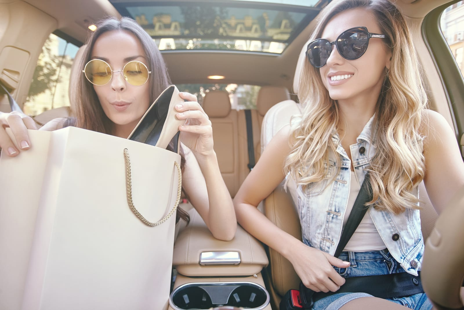 smiling girls sitting in the car after shopping