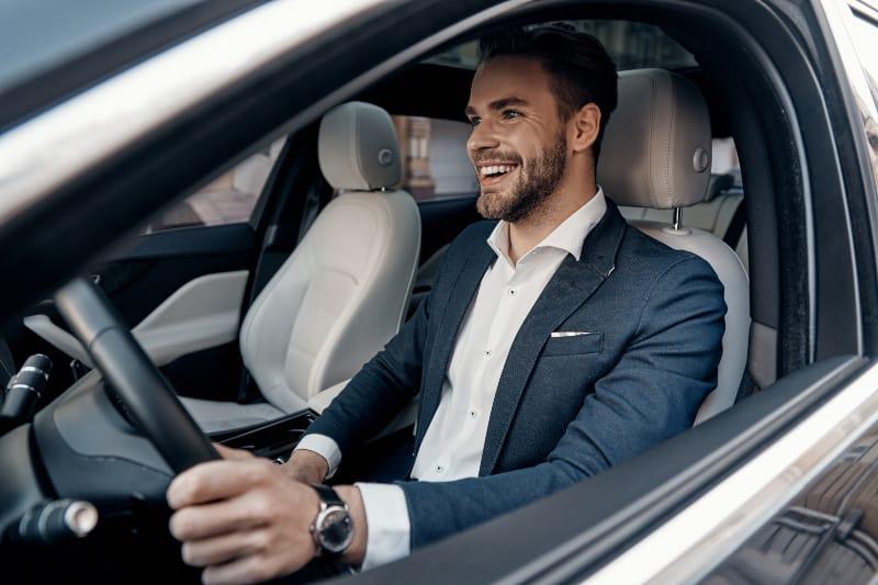 smiling man in suit driving car