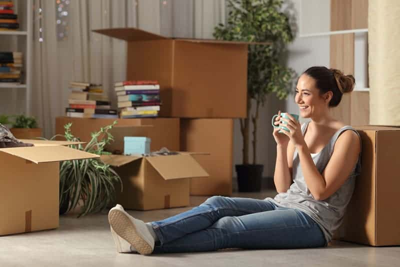 smiling woman sitting on floor at home