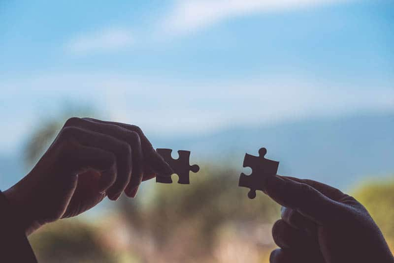 two hands holding two pices of puzzle