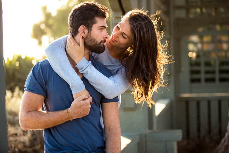 woman hugging man from back and looking at each other