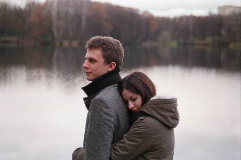 woman hugging man from back beside lake