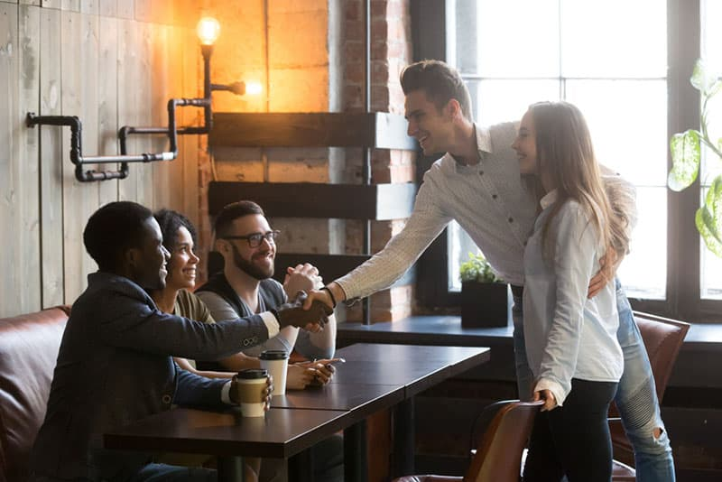 woman introducing a man to her friends
