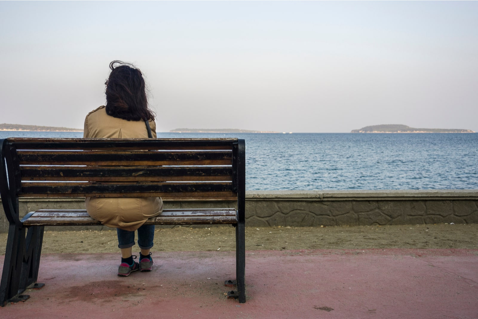 woman sit alone on bench, looking at distant sea