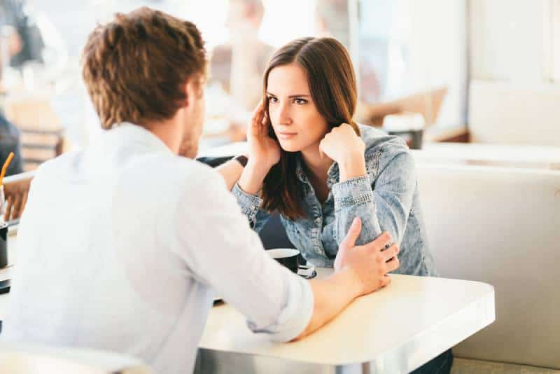 woman suspiciously looking at man while he holding her arms in cafe