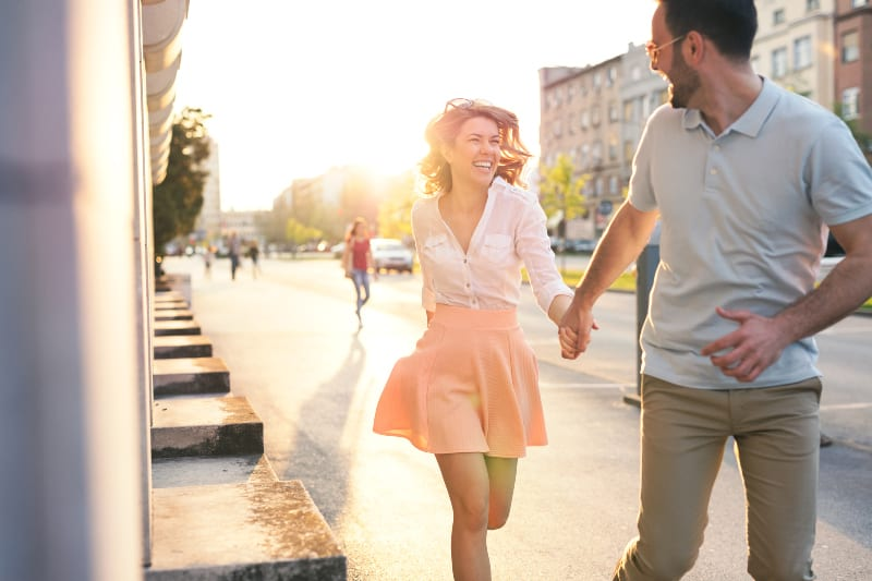 woman wearing pink skirt running with her smiling man on street