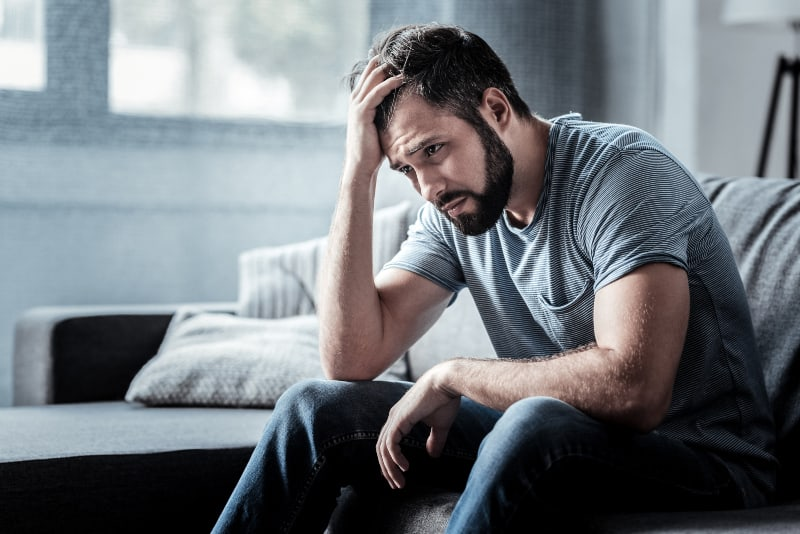 worried bearded man sitting on couch