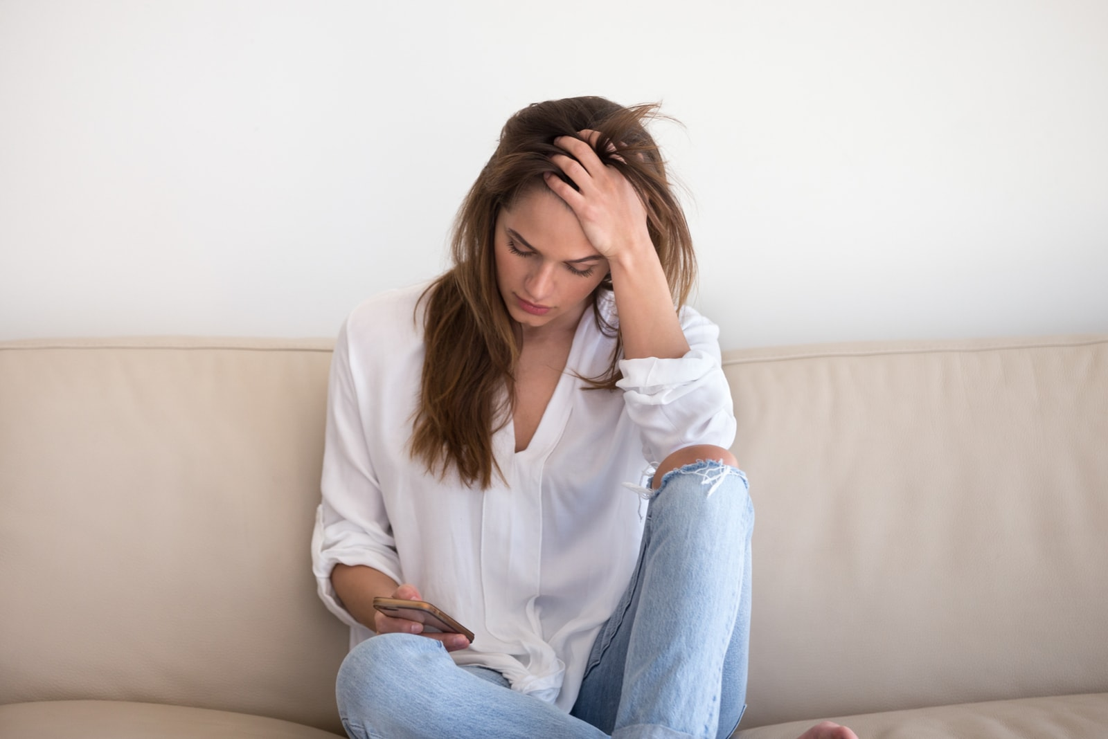 worried woman texting on the mobile phone