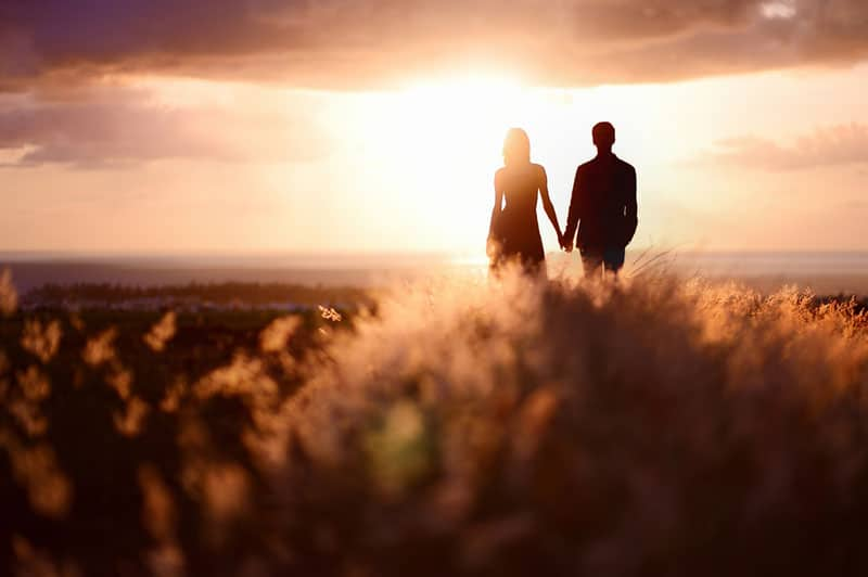 young couple standing in the field