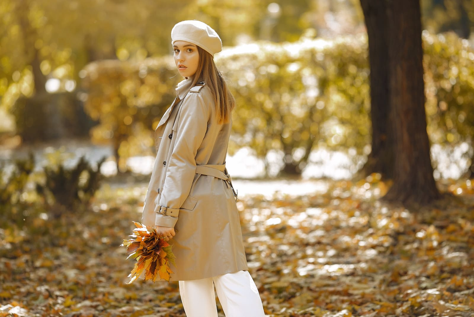 young woman holding leaves in park