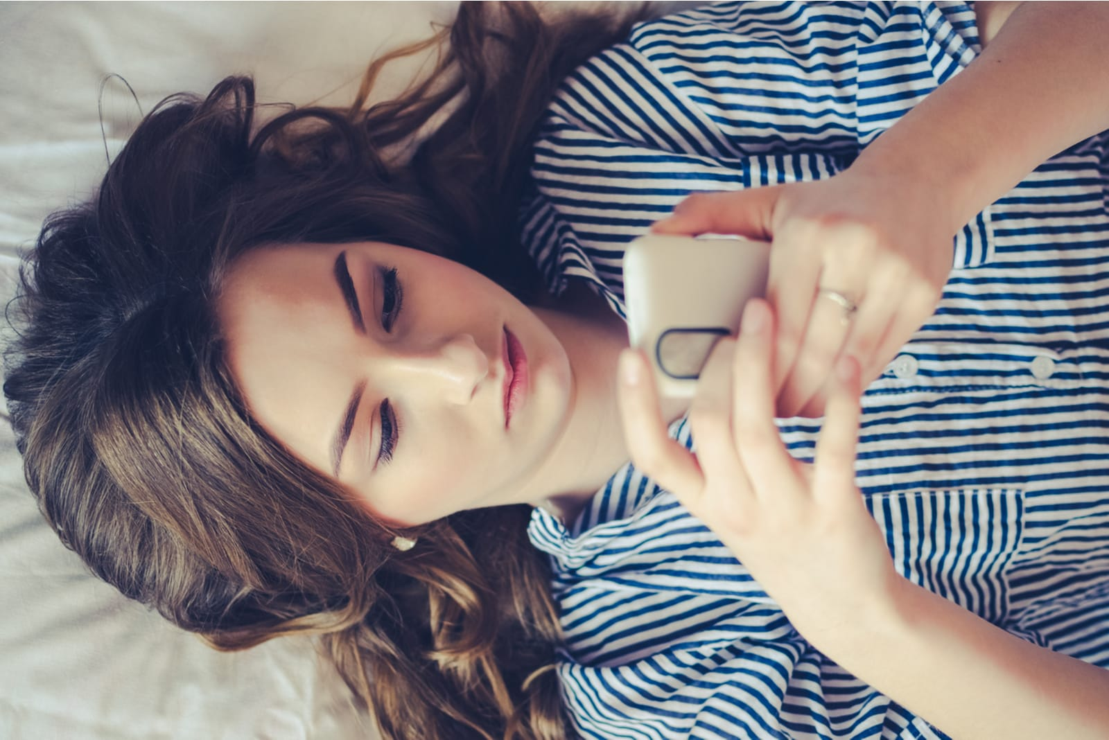 young woman lying in bed and texting on phone
