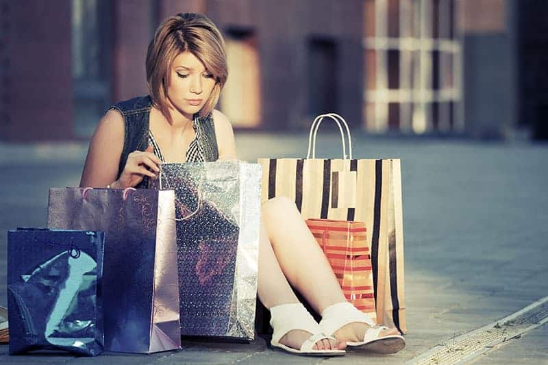young woman sitting on the floor with shopping bags