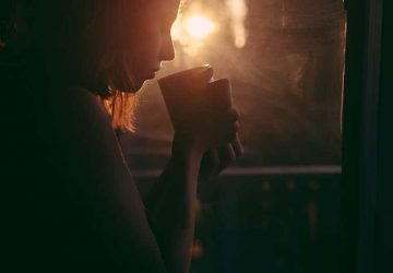 silhouette of woman holding cup of tea