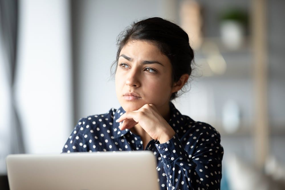 pensive woman sitting by the laptop