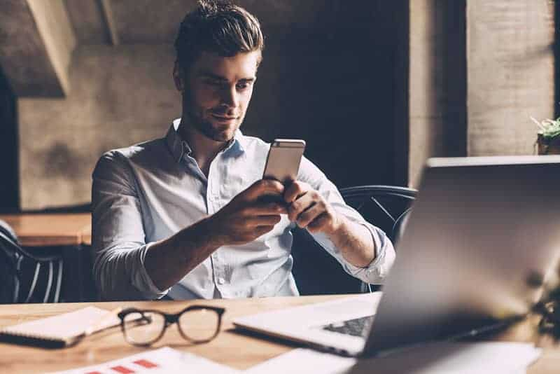 Confident young man in smart casual wear holding smart phone
