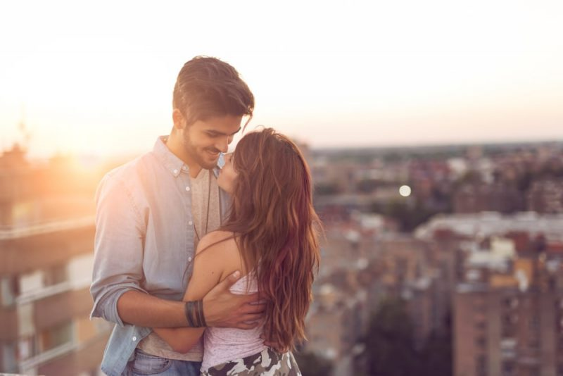 Couple in love standing and hugging on a building rooftop