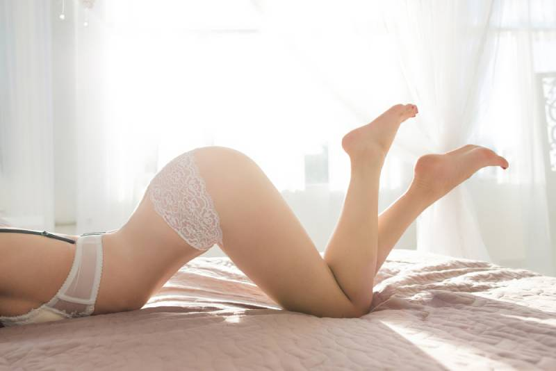 Female body in erotic posture on bed